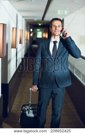 Businessman Walking In Hotel With Smartphone