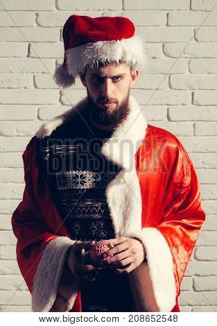 Hipster in coat and hat with decoration toy. New year guy on white brick wall background. Winter holiday and vacation. Xmas party celebration. Christmas man with long beard.