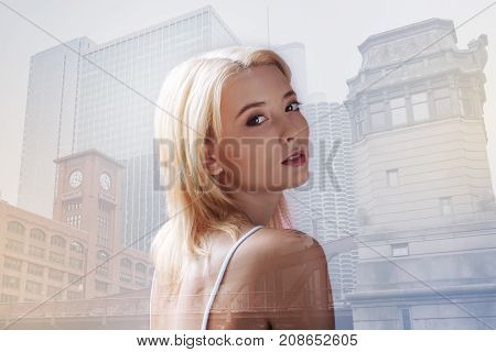Having a stroll. Close up of adorable girl expressing calmness while walking through the city