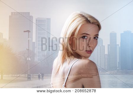 Expressing calmness. Close up of beautiful blonde girl looking at you while standing in urban surrounding