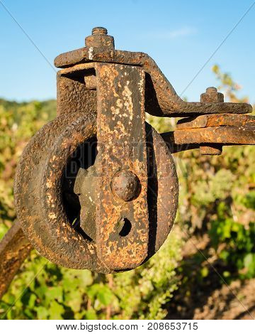 Old rusted pulley of an old well in a vineyard