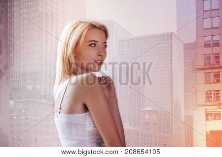 Lost in thoughts. Charming girl standing against city background while looking at the distance and expressing optimism