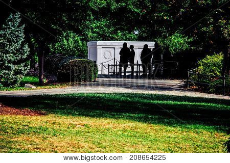 Silhouettes of tourists visiting the Tomb of the Unknown Soldier at Arlington National Cemetery in Virginia.