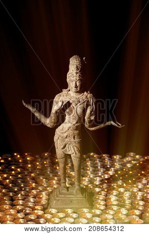 Diwali Festival of Light. Hindu goddess Lakshmi in divine candle light. Traditional religious holiday of Deepavali depicted with bronze statue of Laxmi and hundreds of tealight candles.