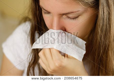 Girl blowing his nose into a white handkerchief. Runny nose. Closeup.