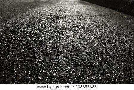 Asphalt after the rain. Texture of asphalt road. Light reflection on asphalt. Grunge asphalt. Asphalt background. Asphalt texture. Asphalt road.