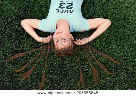 Sporty pretty teen girl loves sports.teenage girl lying on the grass top view.The hair on the head many braids.