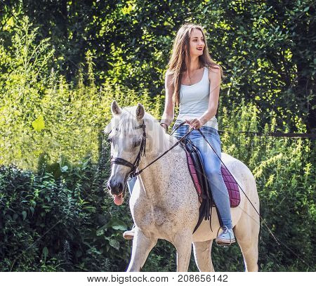 A beautiful girl is riding a white horse. Sincere emotions.