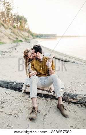 A romantic couple is hugging on the beach. Beautiful girl embrace her boyfriend from back. Wedding. Artwork, soft focus