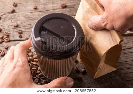 Coffee and snack for breakfast. The man takes a cup of coffee and a paper bag with a snack to go