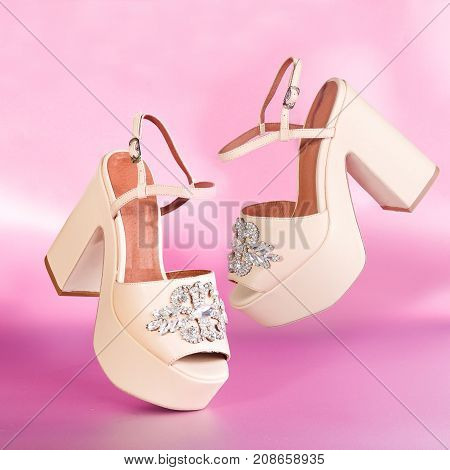 The pair of beautiful beige sexy high sandals on a pink background. Women's high sandals soar above table on pink background