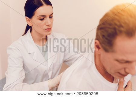 Seriousness. Attentive brunette woman sitting behind her patient and being in uniform while examining pain in back