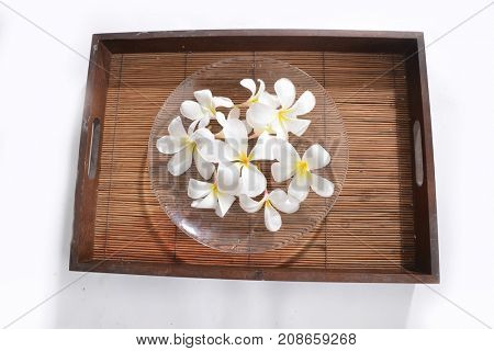 Many white frangipani, in bowl, , towel, on mat