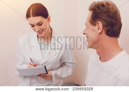 Write prescription. Delighted woman wearing smock and expressing positivity while sitting near her patient