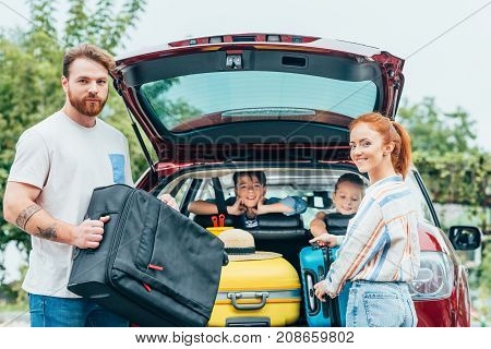 Family Packing Luggage In Trunk