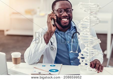 Good news. Radiant millennial man in a labcoat smiling cheerfully while sitting at his table and looking at a three dimensional model of DNA during a pleasant phone conversation alone.