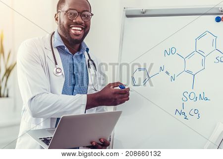 Positivity is the key to success. Excited young doctor smiling cheerfully while standing at a presentation board with a laptop in hands and drawing a chemical formula with a colorful marker.