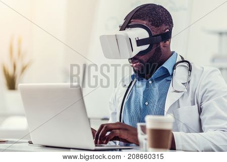Advanced specialist. Millennial doctor with a stethoscope focusing his attention on a screen of his laptop and typing while sitting at a table and wearing a virtual reality glasses at work.