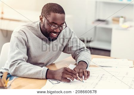 Young but professional. Calm and joyful male engineer slightly smiling while focusing his attention on a piece of paper and working on a technical project with a pencil in his hand alone.