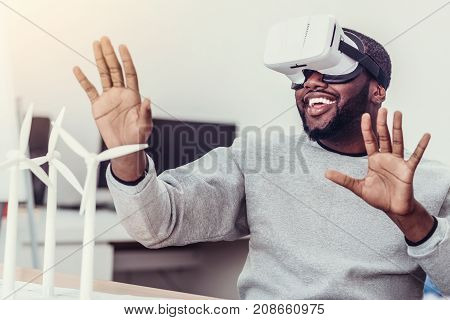 Hey. Positive minded millennial guy in casual getting excited and gesturing while sitting at a table and trying on a VR goggles.