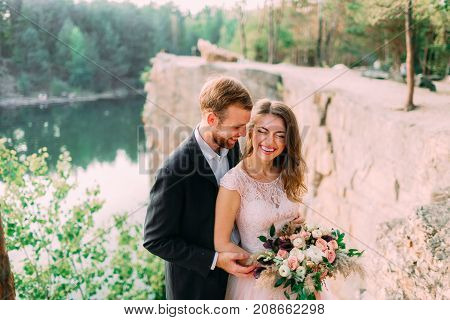 Attractive couple newlyweds bride and groom laugh and smile, happy and joyful moment. Wedding ceremony outdoors. Close-up portrait
