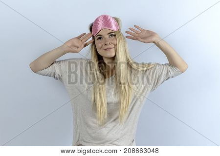young woman in pajamas and blindfolds woke up in a great mood. Portrait of relaxed and happy women awake on white background