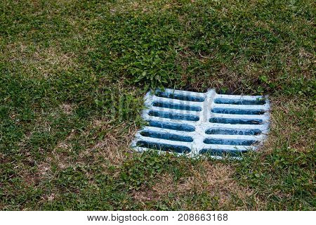 blue outdoor old square water drain in grass