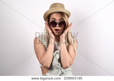 young pretty woman posing for a portrait with a surprised excited shocked face. Reaction to the promotion of sales. Denim dress hat and white top sunglasses. Emotional look into the camera white background