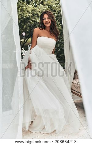 Best day ever. Full length of attractive young woman in wedding dress looking at camera and smiling while standing outdoors
