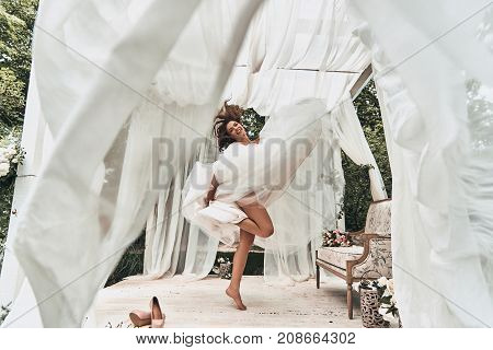Playful bride. Full length of attractive young woman in wedding dress smiling while dancing in the wedding pavilion outdoors