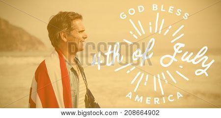 Digitally generated image of happy 4th of july message against man wrapped in amrican flag standing on beach