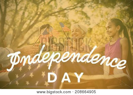 Independence day text against white background against happy family having a picnic