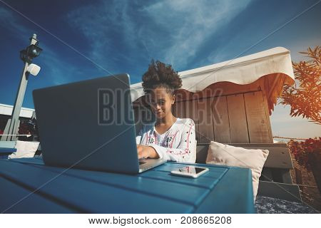 Smiling beautiful young African American female student is studying using laptop outdoors; cheerful black curly freelancer girl is sitting in a park and using her netbook for surfing social networks