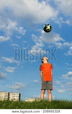 Ekaterinburg, Russia - August 18, 2017: Nikita Dorokhin (8 years old) from Nizhny Tagil, looks at a ball thrown into the air