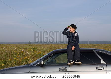 Ekaterinburg, Russia - August 28, 2017: Nikita Dorokhin (8 years old) from Nizhny Tagil, sits on the roof of Lada Priora and looks into the distance