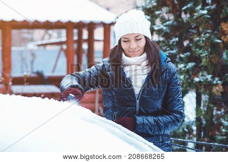 Young Attractive Woman In Winter Clothes Removes Snow From Car With Snow Brush.