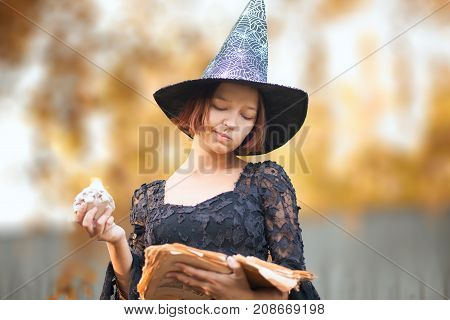 Young woman dressed like a witch ready for halloween looking at the spell book. Fall outdoors.