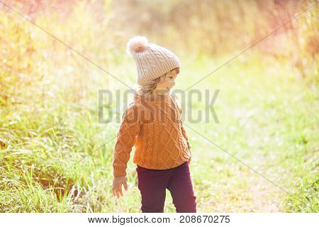 Autumn outdoor portrait of happy child girl walking in forest in warm knitted sweater and hat toned photo.