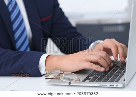 Businessman working by typing on laptop computer. Man's hands on notebook or business person at workplace. Employment  or start-up concept.