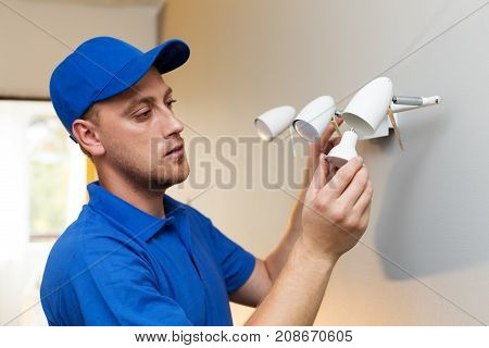 electrical maintenance - electrician change light bulb in wall lamp