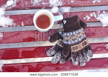 Mug Of Tea And Women's Knitted Gloves On A Bench In The Winter, The Snow Below. Top View