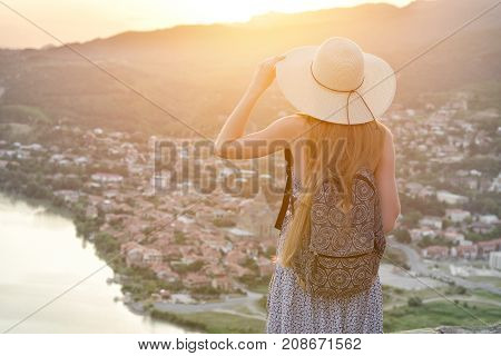Girl With A Backpack And In A Hat Looks At The City And The River Below. Back View