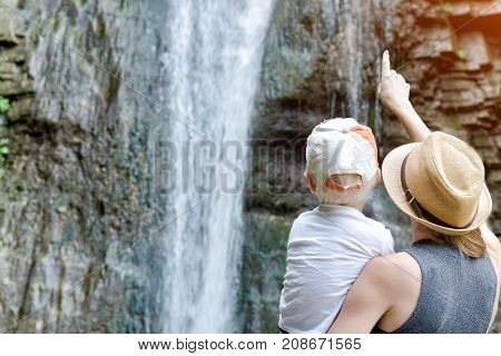 Mom Shows His Son A Waterfall, A View From The Back.