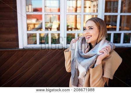 ttractive blonde woman in urban background with sun backlight. Young girl wearing winter coat and scarf standing in the street. Pretty female with straight hair hairstyle and blue eyes.