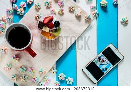 Top of view candy , fruit salad cake , coffee and phone on blue and white table