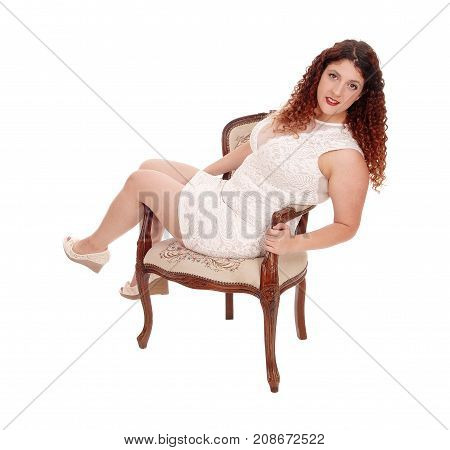 A young pretty woman in a beige dress sitting in an armchair with booths legs over the side isolated for white background
