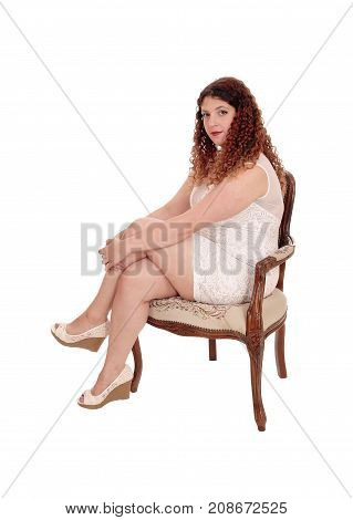 A full figured young woman sitting in a beige lace dress on an armchair with curly brunette hair isolated for white background