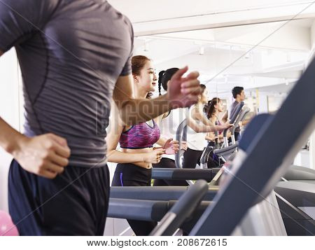 young asian adult working out on treadmill focus on the girl in the middle.