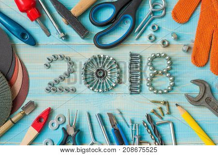 Happy new year 2018 composition with screws, nails,  bolts , dowels and tools on blue wooden background. New year. New year background. Industrial new year.