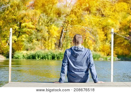 Young Man Is Sitting On The Dock. Autumn, Sunny. Back View